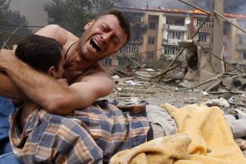 A Georgian man cries as he holds the body of his relative after a bombardment in Gori, 80 km (50 miles) from Tbilisi, August 9, 2008. A Russian warplane dropped a bomb on an apartment block in Gori on Saturday, killing at least 5 people, a Reuters reporter said. The bomb hit the five-story building close to  Georgia's embattled breakaway province of South Ossetia when Russian warplanes carried out a raid against military targets around the town.  REUTERS/Gleb Garanich  (GEORGIA)  FOR BEST QUALITY also see: GF2E4CE0T8K01 - RTR20TEA