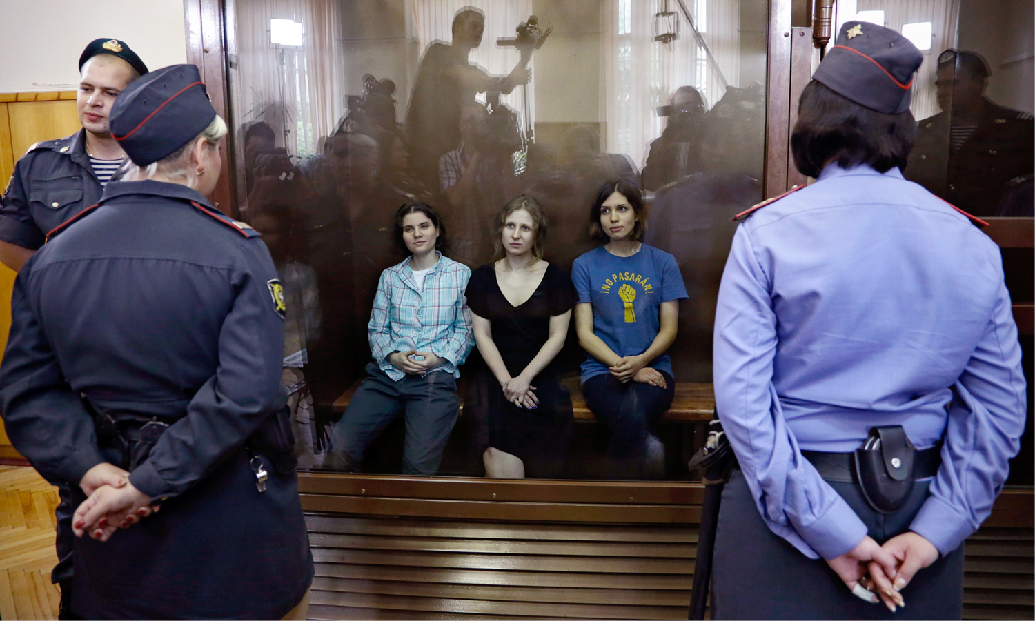 "Feminist punk group Pussy Riot members, from left, Yekaterina Samutsevich, Maria Alekhina and Nadezhda Tolokonnikova sit in a glass cage at a court room in Moscow, Russia on Friday, Aug 17, 2012. The women, two of whom have young children, are charged with hooliganism connected to religious hatred but the case is widely seen as a warning that authorities will only tolerate opposition under tightly controlled conditions. T-shirt on right worn by Tolokonnikova is Spanish and translates to ""They shall not pass"", a slogan often used to express determination to defend a position against an enemy. (AP Photo/Sergey Ponomarev)"